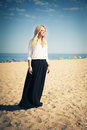Young beautiful woman blonde poses on a beach dressed in white shirt and black skirt fashion model Royalty Free Stock Photo