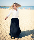 Young beautiful woman blonde poses on a beach dressed in white shirt and black skirt fashion model Royalty Free Stock Image