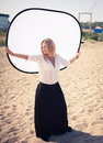 Young beautiful woman blonde poses on a beach dressed in white shirt and black skirt fashion model Royalty Free Stock Photos