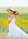 Young beautiful woman on blooming sunflower field in summer Royalty Free Stock Photo