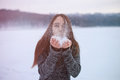 Young beautiful woman blowing snow in winter park Royalty Free Stock Photo