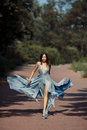 Young beautiful woman blue dress walking path in park. Royalty Free Stock Photo