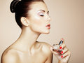 Young beautiful woman with bottle of perfume. Perfect Makeup Royalty Free Stock Photo