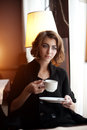 Young beautiful woman in a cafe. Modern trendy blondy girl in re Royalty Free Stock Photo