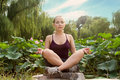 Young beautiful woman do yoga and meditate in the park with lotus flowers Stock Photos