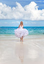 Young beautiful woman in a dress of the bride runs on waves of the sea Royalty Free Stock Photography