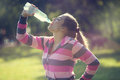 Young beautiful woman drinking water after exercising in the par city park Royalty Free Stock Photography