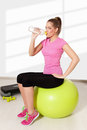 Young beautiful woman drinking water during workout light background Stock Images