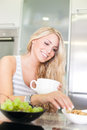 Young beautiful woman enjoying healthy breakfast in the kitchen Royalty Free Stock Image