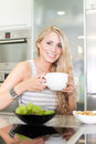Young beautiful woman enjoying healthy breakfast in the kitchen Stock Photography
