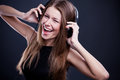 Young beautiful woman enjoying the music on headphones listening to a dance Stock Images