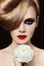 Young beautiful woman fancy hairdo smoky eyes holding white flower her hand Royalty Free Stock Image