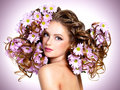 Young beautiful woman with flowers in hairs posing at studio Stock Photos