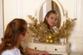 Young beautiful woman in front of the mirror getting ready for holiday christmas Stock Images