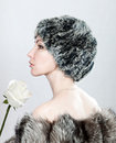 The young beautiful woman in fur and with a white rose Stock Photography