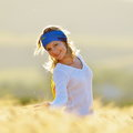 Young beautiful woman on golden cereal field in summer happy Stock Images