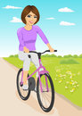 Young beautiful woman having fun riding bicycle on a dirt road in countryside Royalty Free Stock Photo