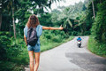 Young beautiful woman hitchhiking standing on road Royalty Free Stock Photo
