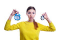 Young beautiful woman holding big and small clocks with surprise Royalty Free Stock Photo