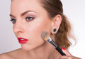 Young beautiful woman holding a brush and applying her make-up Royalty Free Stock Photo