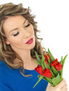 Young beautiful woman holding a bunch of tulips dslr royalty free image attractive thoughtful with dark blonde highlighted curly Royalty Free Stock Image