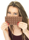 Young Beautiful Woman Holding a Chocolate Bar Over Mouth Royalty Free Stock Photo