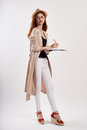 Young beautiful woman holding documents and pen on white isolated background, full-length photo, fashion, beauty