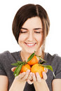 Young beautiful woman holding fresh tangerines Royalty Free Stock Photos