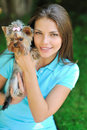 Young beautiful woman holding her puppy dog - outdoor portrait