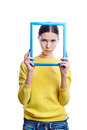 Young beautiful woman holding light blue frame with sad expressi expression isolated on white background Stock Photo