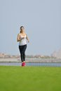 Young beautiful woman jogging on morning and running at park in the city in sport outdoors health and fitness concept Royalty Free Stock Photos