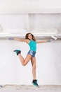 Young beautiful woman jump and paints the wall with white paint Royalty Free Stock Photo