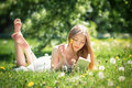 Young beautiful woman lies on a grass and reads the book Royalty Free Stock Photo