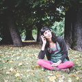 Young beautiful woman listening to music autumn at the park in Royalty Free Stock Photos