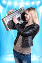 Young beautiful woman listening to music holding a retro tape recorder. Royalty Free Stock Photo