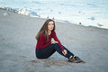 young beautiful woman with long hair, in black jeans and red shirt, sitting on sand on beach among seagulls birds Royalty Free Stock Photo