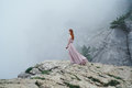 Young beautiful woman in a long pink dress is standing near a mountain cliff in the fog Royalty Free Stock Photo