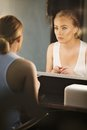 Young beautiful woman looking at herself in mirror the attractive caucasian female model Royalty Free Stock Image