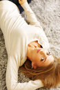 Young beautiful woman lying on the carpet at home Stock Image