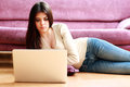 Young beautiful woman lying on the floor and using laptop at home Stock Photo