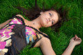 Young beautiful woman lying on a green grass Royalty Free Stock Photos