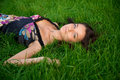 Young beautiful woman lying on a green grass Stock Photography