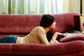 Young beautiful woman lying on the sofa with laptop at home Royalty Free Stock Image