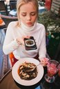 Young beautiful woman making photo of black pasta with seafood and cuttlefish ink