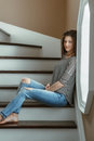 Young beautiful woman model with messy long hair in ripped blue jeans and striped t-shirt sitting indoor by window Royalty Free Stock Photo