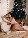 Young beautiful woman near an elegant Christmas tree with gifts just waiting for Christmas Royalty Free Stock Photo