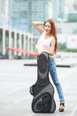 Young beautiful woman posing outdoor with her guitar gig bag model is thai ethnic Stock Photography