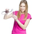 Young beautiful woman pours water into a glass this image has attached release Stock Images