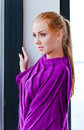 Young beautiful woman in purple jersey the before a window Royalty Free Stock Photography