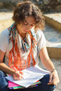 Young beautiful woman reading and writing in excercise book outside with curly hair park Stock Images